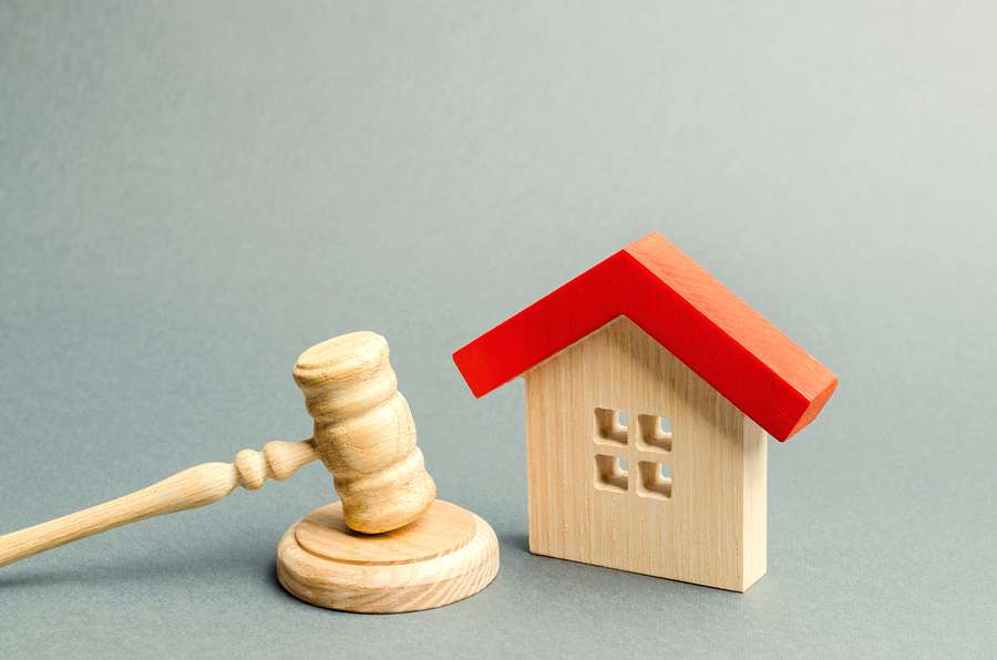 Conveyancing concept: miniature of a home and a gavel